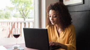 lady in yellow on laptop with wine; online therapist for healthy relationships blog